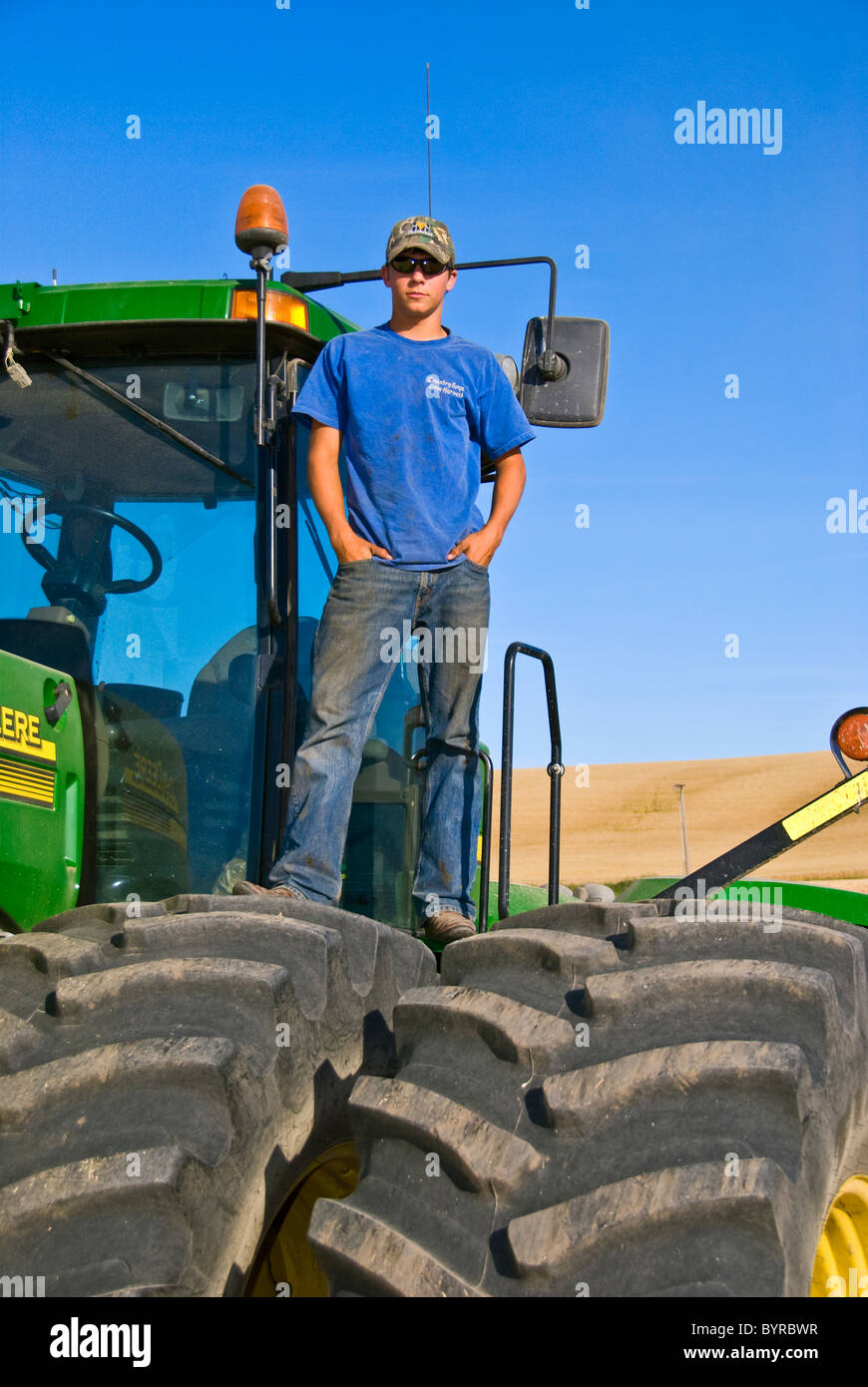 A young farmer atop his tractor during a short break from harvest in the Palouse region / near Pullman, Washington, - Stock Image