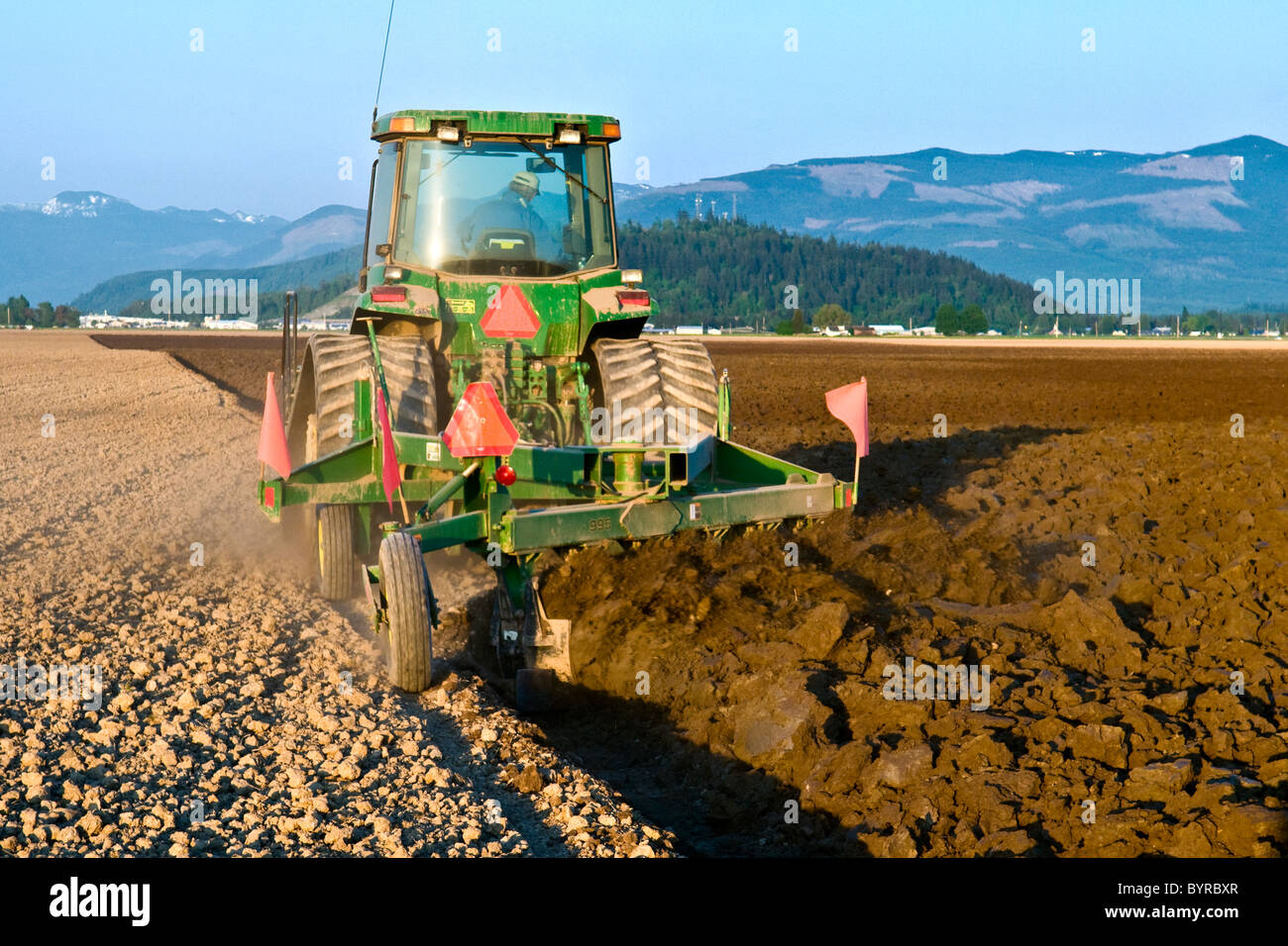 A John Deere tracked tractor pulling a reversible plow prepares a field for planting potatoes / near Burlington, - Stock Image