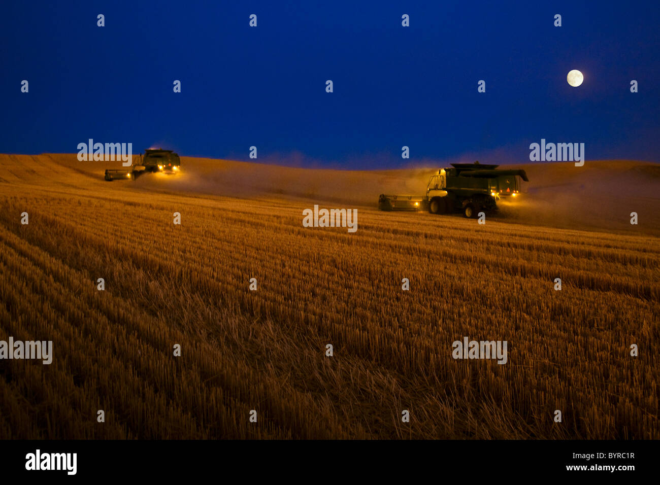 Two John Deere combines harvest wheat after dark with the moon on the rise/ near Pullman, Palouse Region, Washington, - Stock Image