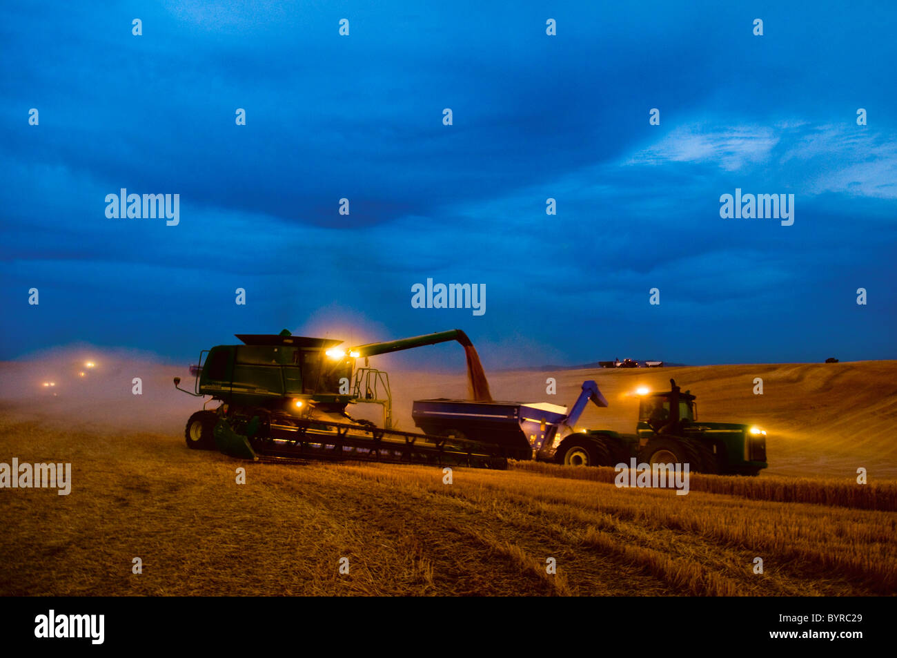 "A John Deere combine harvests wheat while unloading to a grain cart ""on-the-go"" on an early overcast evening / Washington, - Stock Image"
