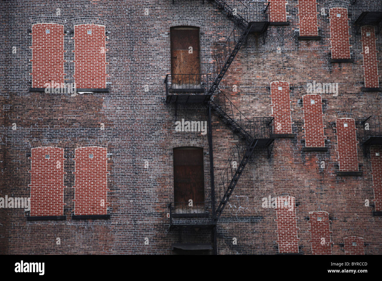a fire escape going up the side of a brick building; manhattan, new york city, new york, united states of america - Stock Image