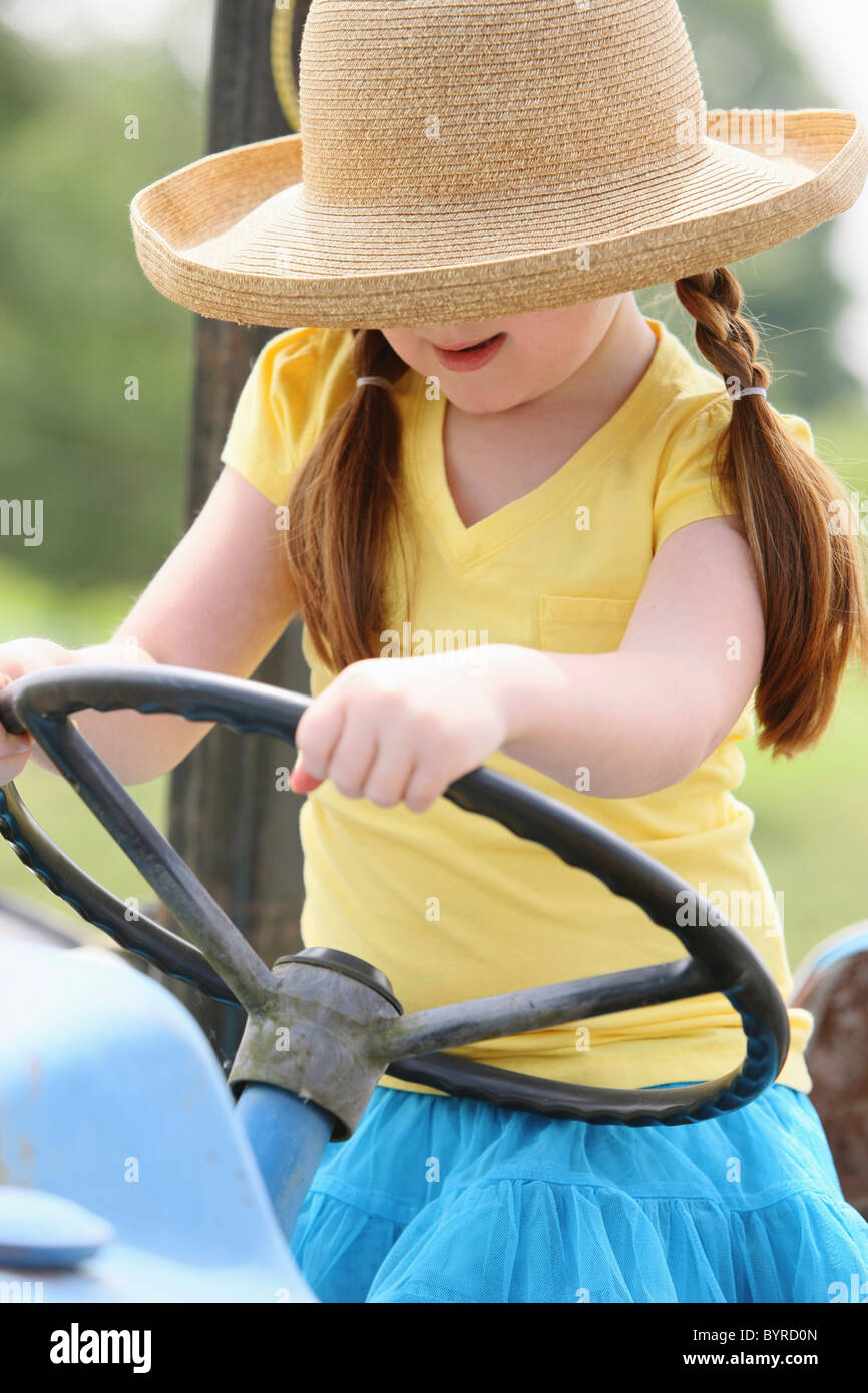 a girl with a straw hat with hands on the steering wheel of a tractor; troutdale, oregon, united states of america - Stock Image