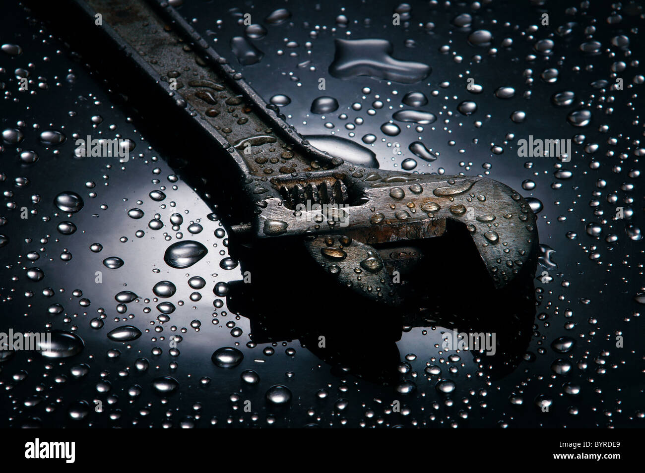 Adjustable spanner , water drops background , wrench - Stock Image