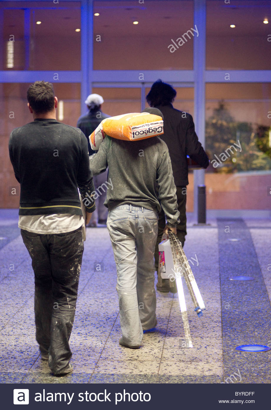 Workmen carrying building materials while walking - Paris France Stock Photo