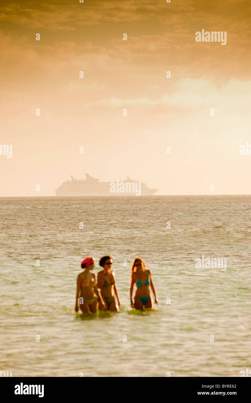 Unidentified cruise liner off the coast of the island of Roatan, Honduras. Three women walking in the sea in the - Stock Image