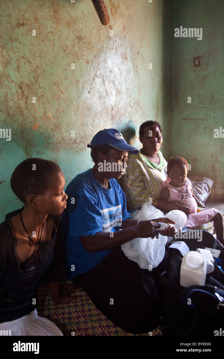 A home health care worker with the NGO Living Goods makes a visit to a woman and her children suffering from malaria - Stock Image