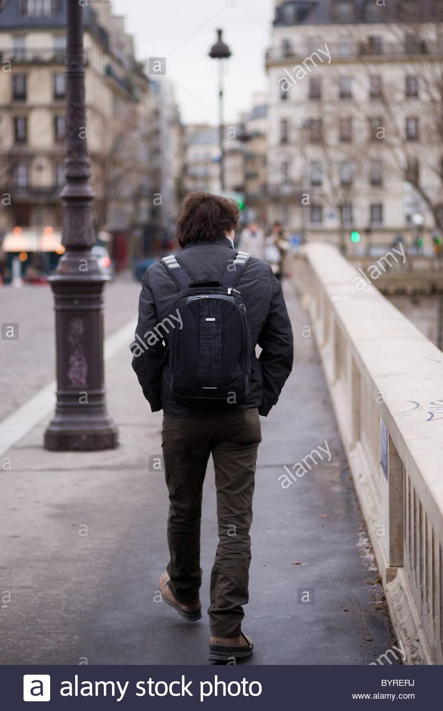River Seine Paris France - Young man walking across a bridge Stock Photo