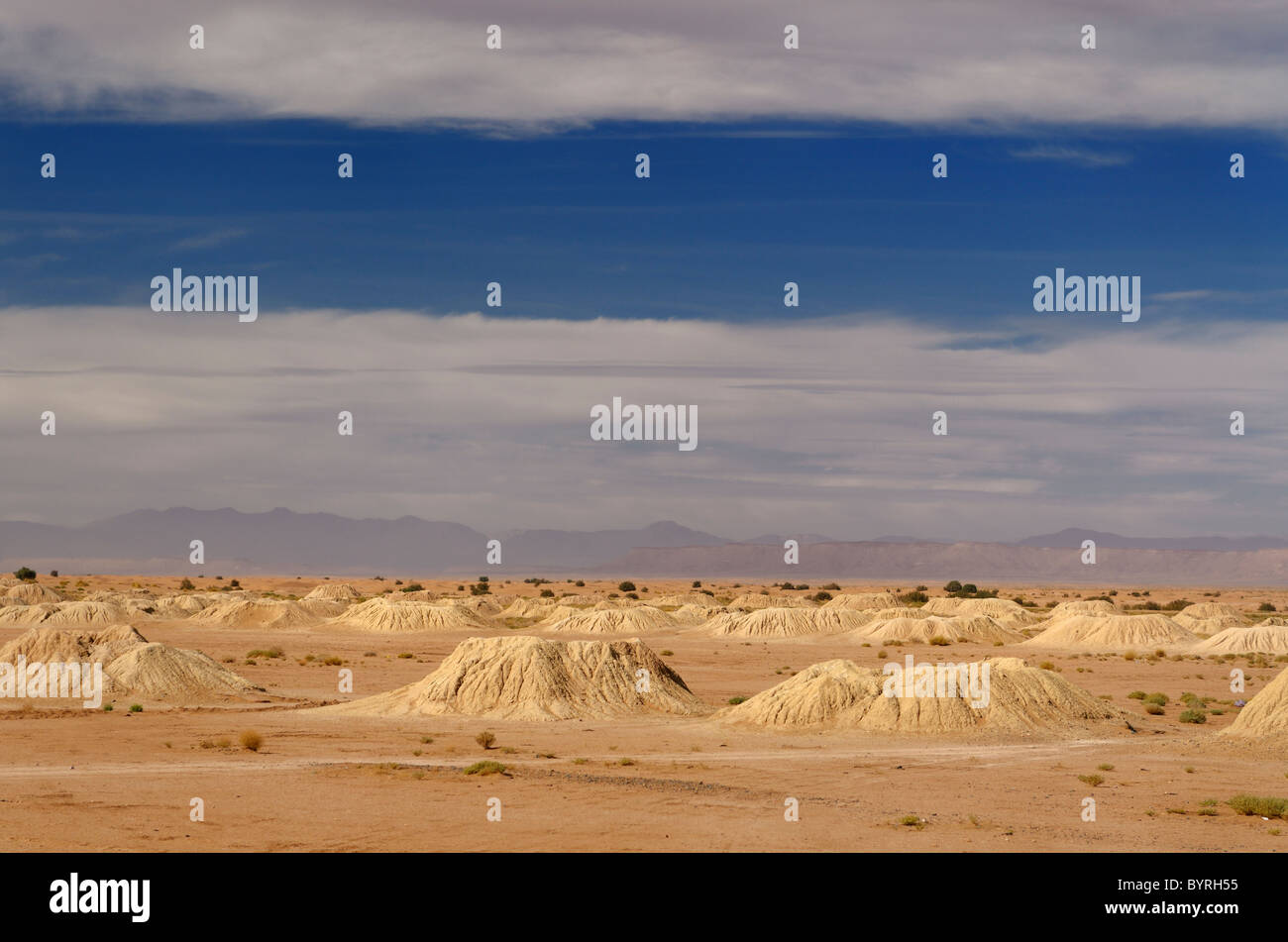 Many ancient earth mound Khettara wells in the Tafilalt plain with High Atlas mountains Morocco - Stock Image