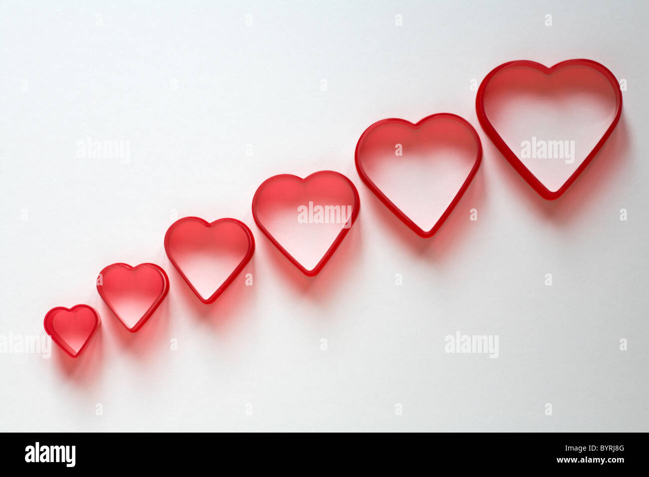 Row of red heart shaped cutters increasing in size isolated against white background - concept falling in love - Stock Image