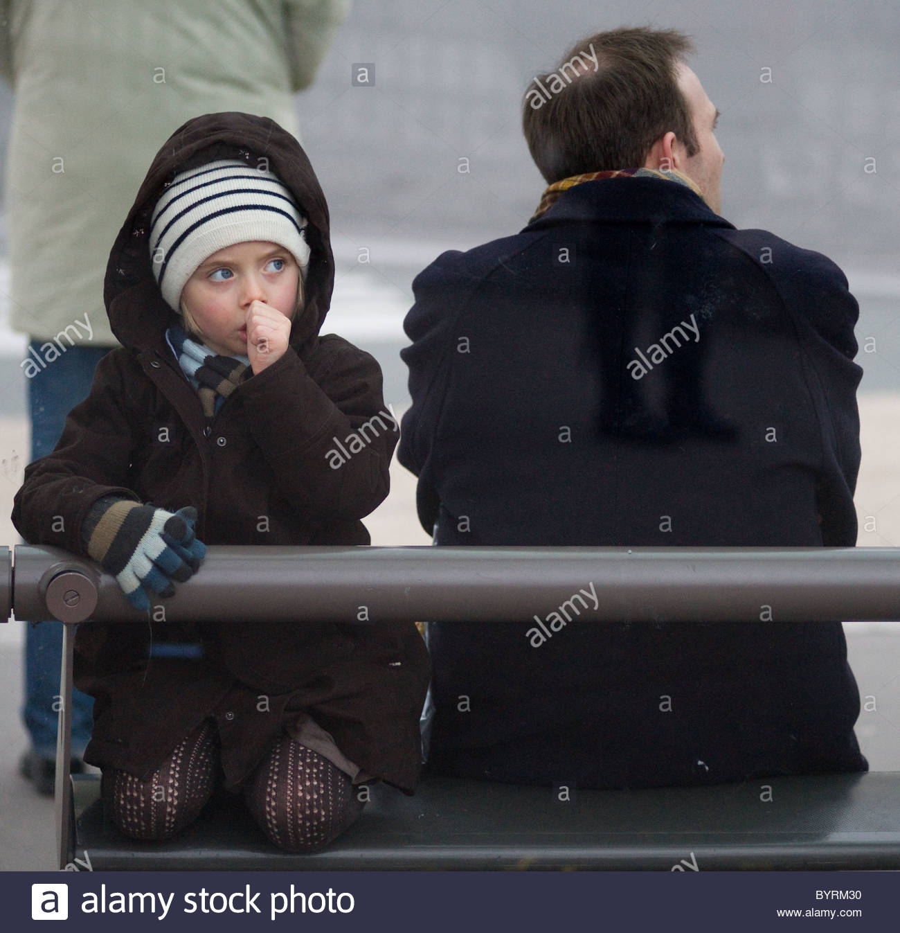 Young girl sucking her thumb waiting at a bus stop with her father - Paris France - French children TODDLER - Stock Image