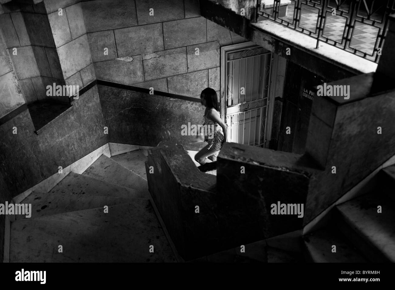 A woman claiming the stairs on an old residential house in Havana, Cuba - Stock Image