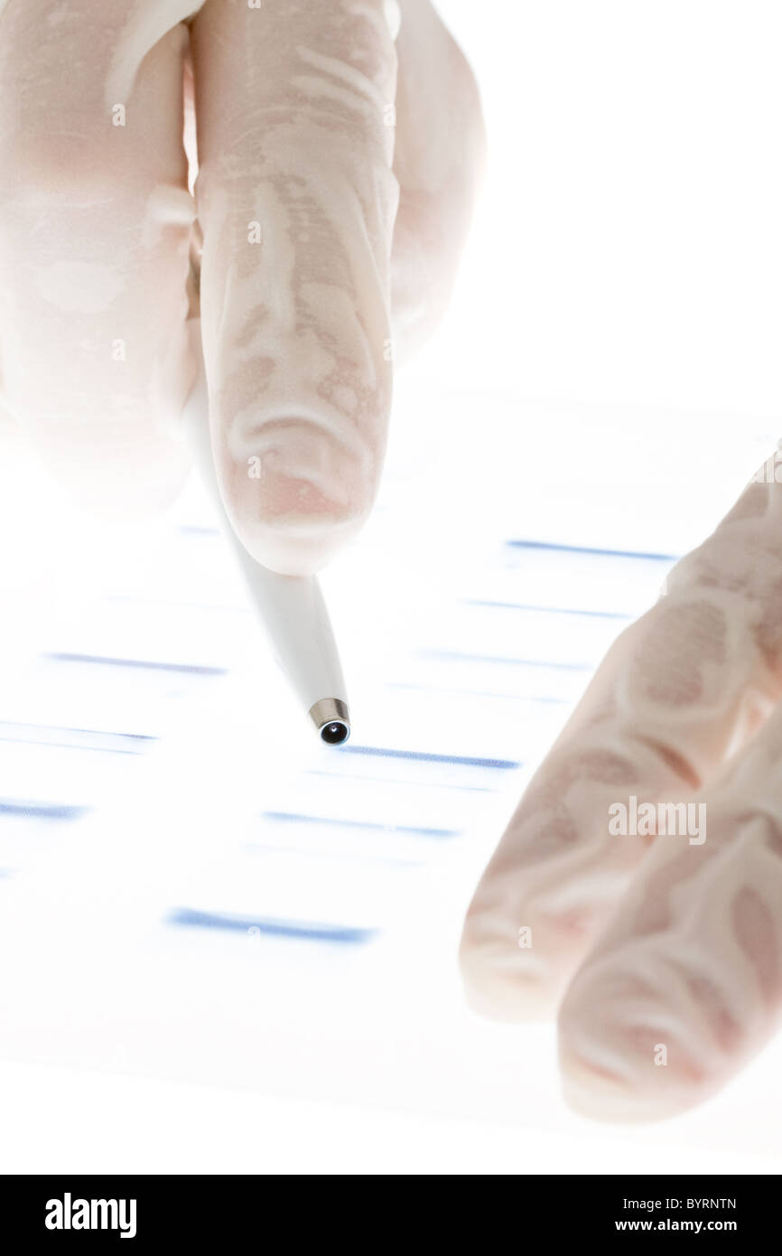 Researcher examining DNA sequence transparency slide - Stock Image