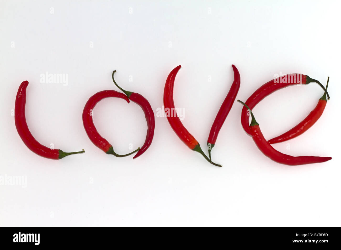 Red hot chili peppers arranged as the word LOVE on white background - Stock Image