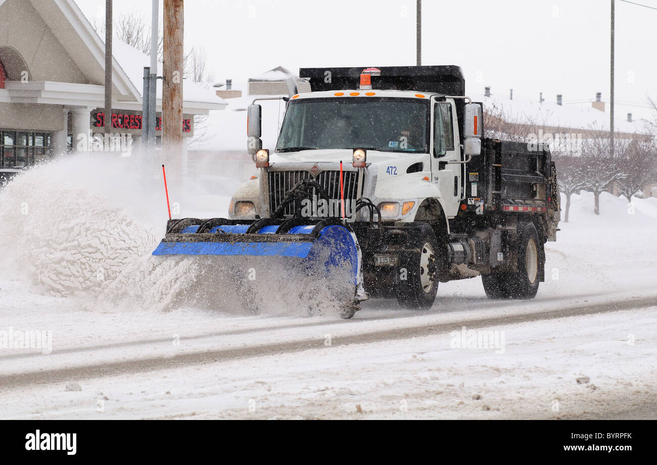 A snowplow clears a city street after a snowstorm - Stock Image