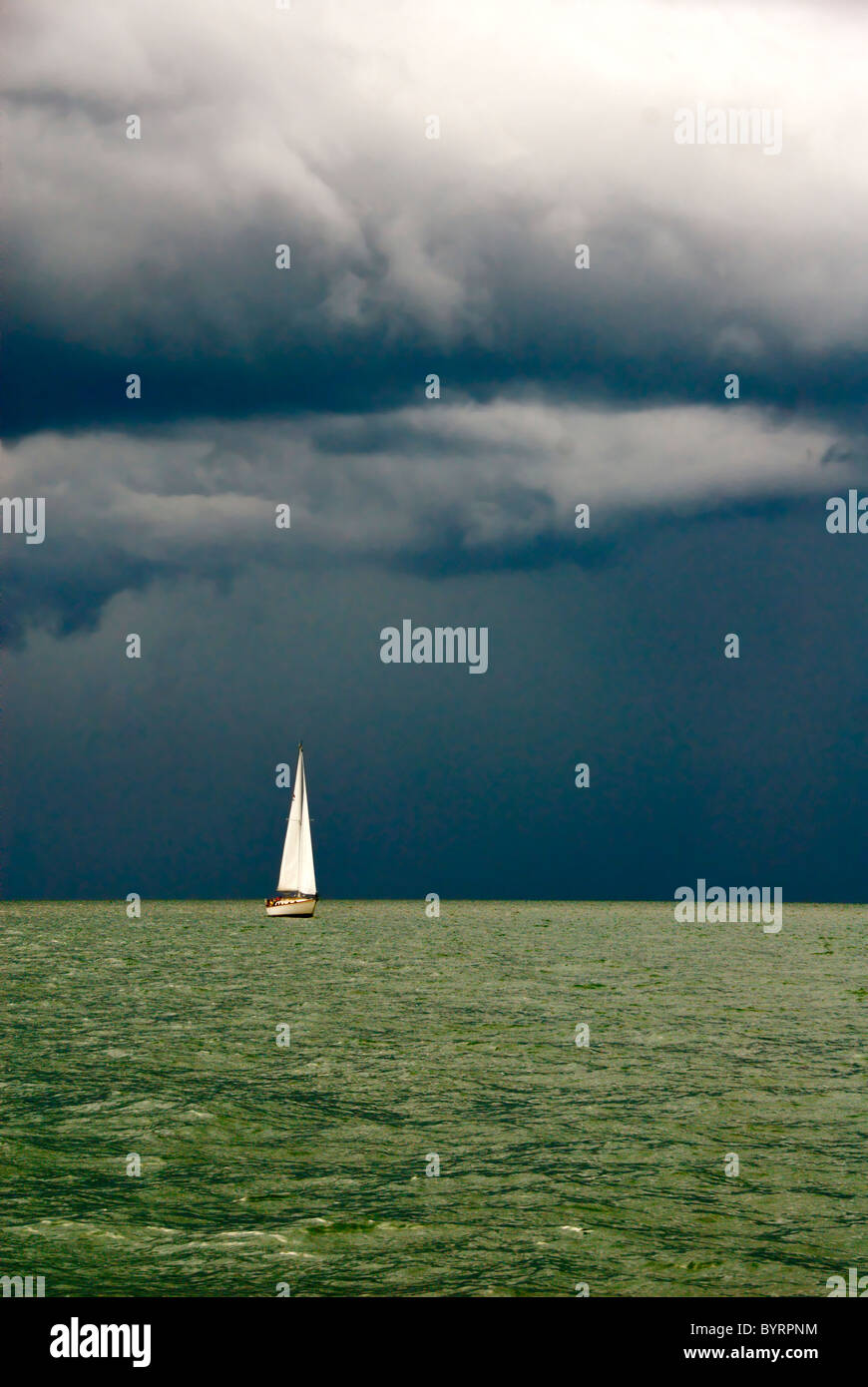 Sailboat in Storm with Green Seas - Stock Image
