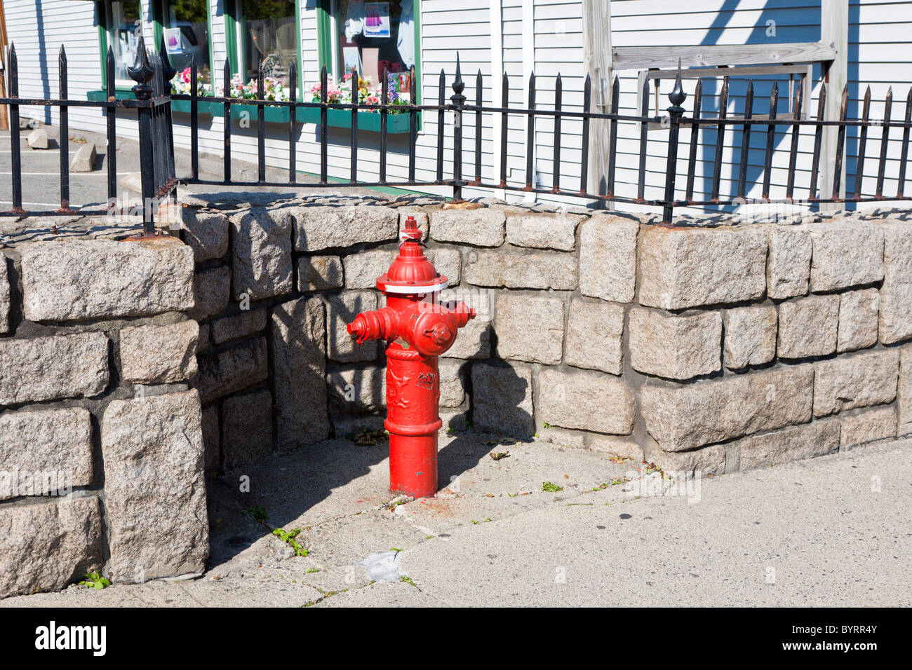 Cutout in granite stone wall around a bright red fire hydrant on Main Street in Bar Harbor, Maine - Stock Image