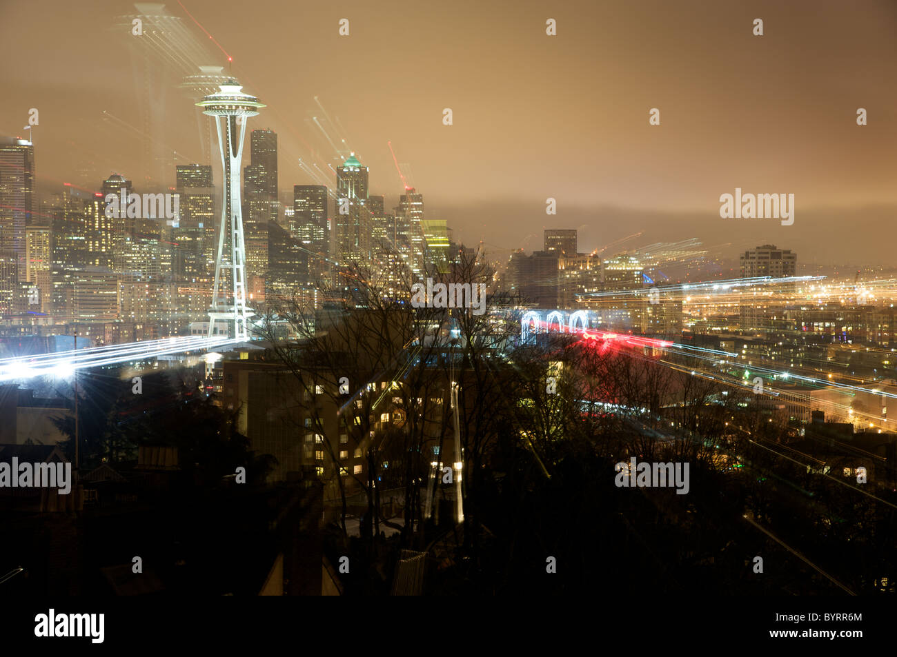 Looking south at downtown Seattle, Washington on a rainy night with the space needle rising high above the city. - Stock Image