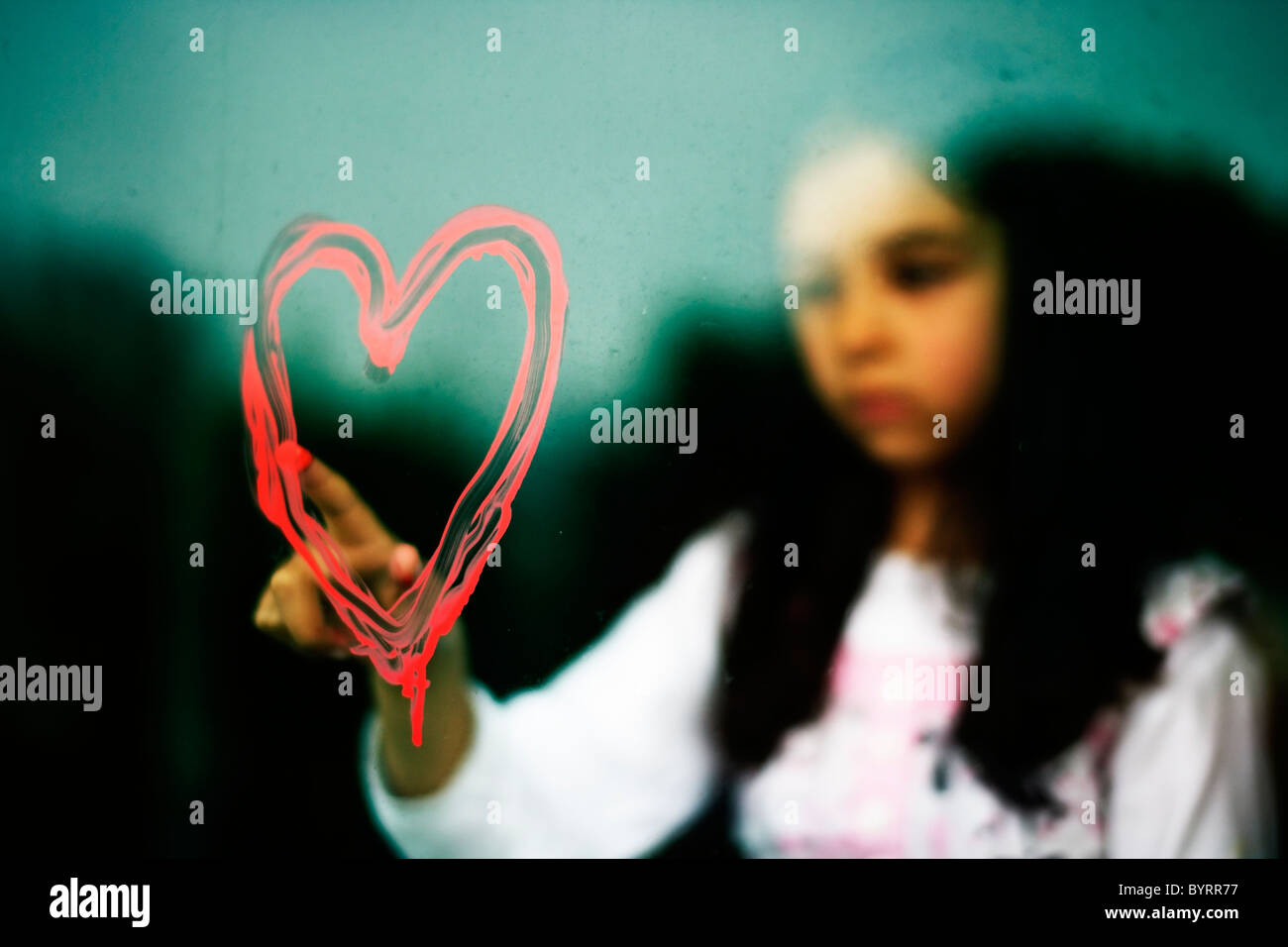 Girl draws heart shape on dirty window with her finger in red paint - Stock Image