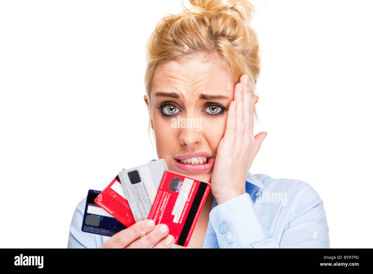 Attractive young woman with debt and money worries - looking stressed holding credit cards - Stock Image