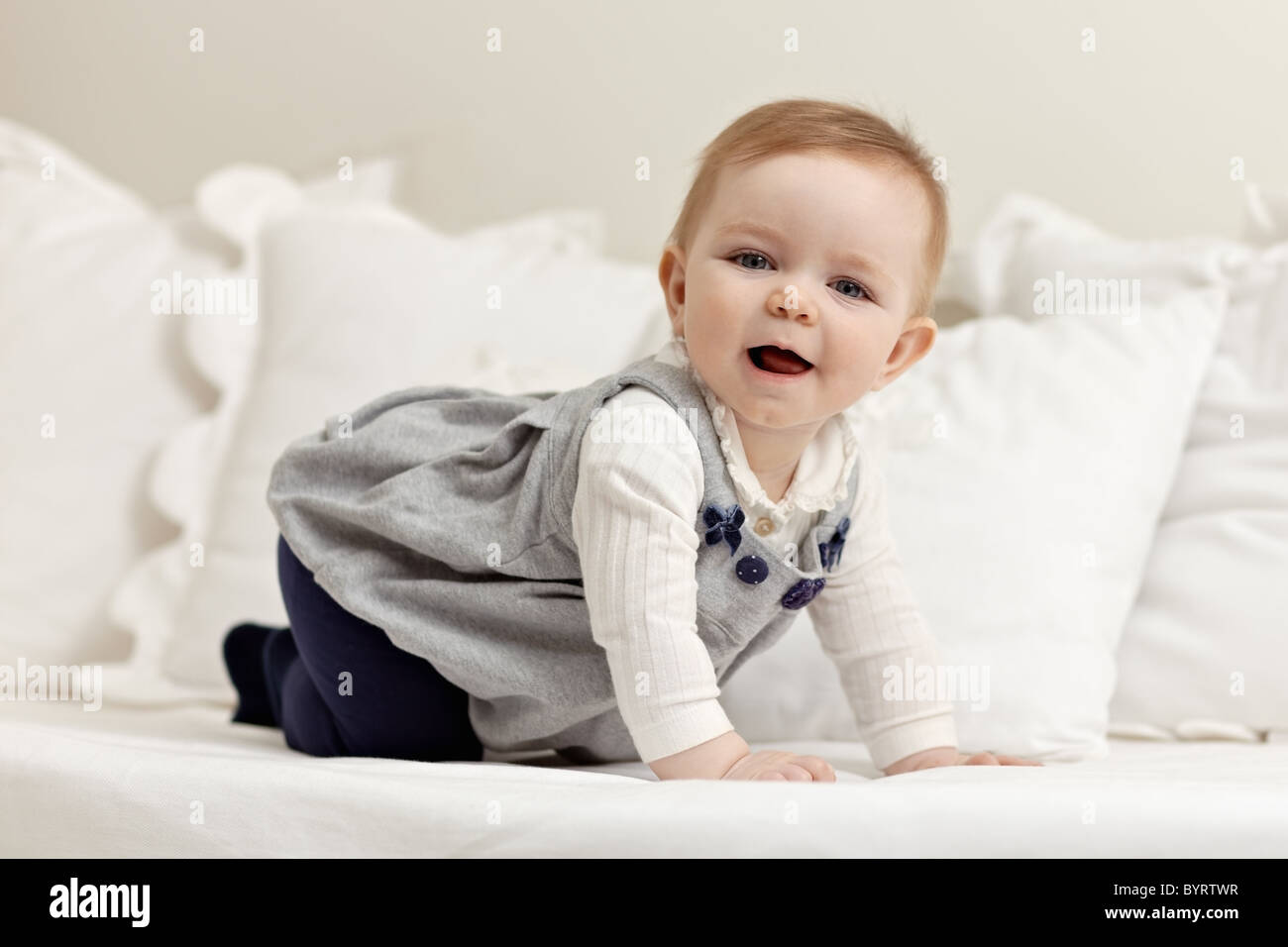 portrait of 6 months female child playing on bed and looking at camera. Horizontal shape, side view, full length - Stock Image