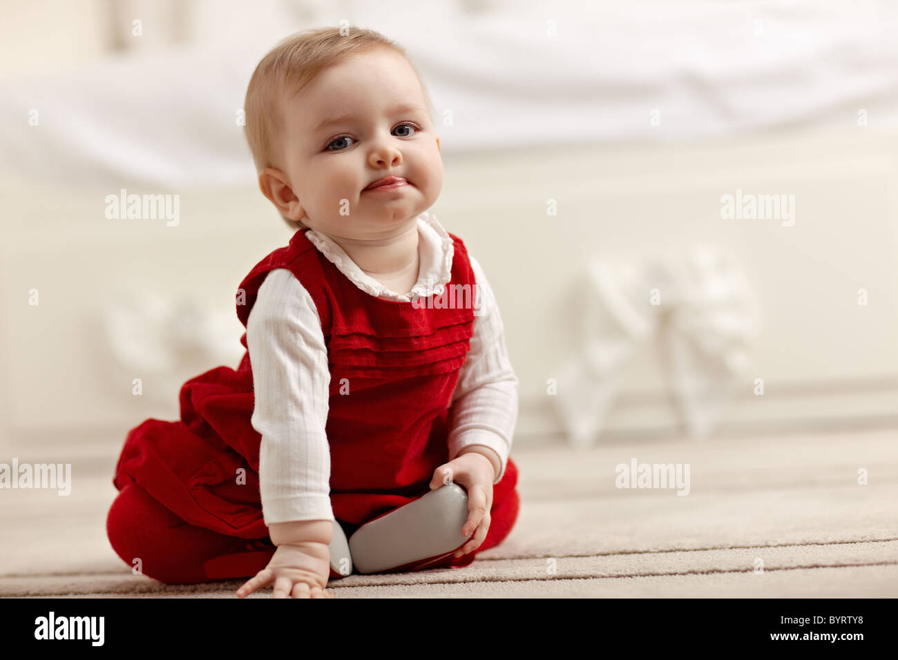 portrait of 6 months female child sitting on floor in red clothes and looking at camera - Stock Image