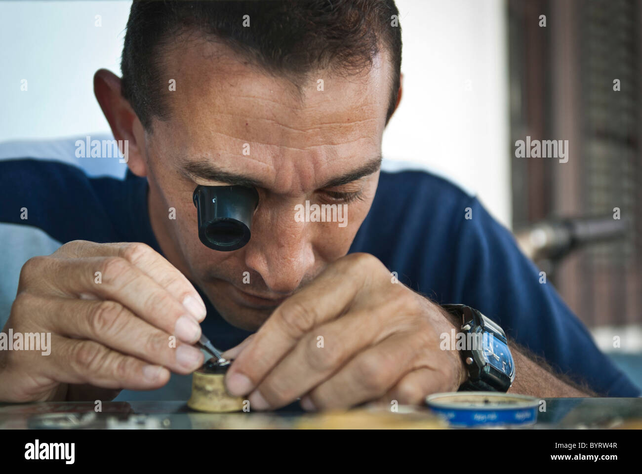Man repairing a watch with a monocle. Santiago de Cuba, Cuba, Caribbean - Stock Image