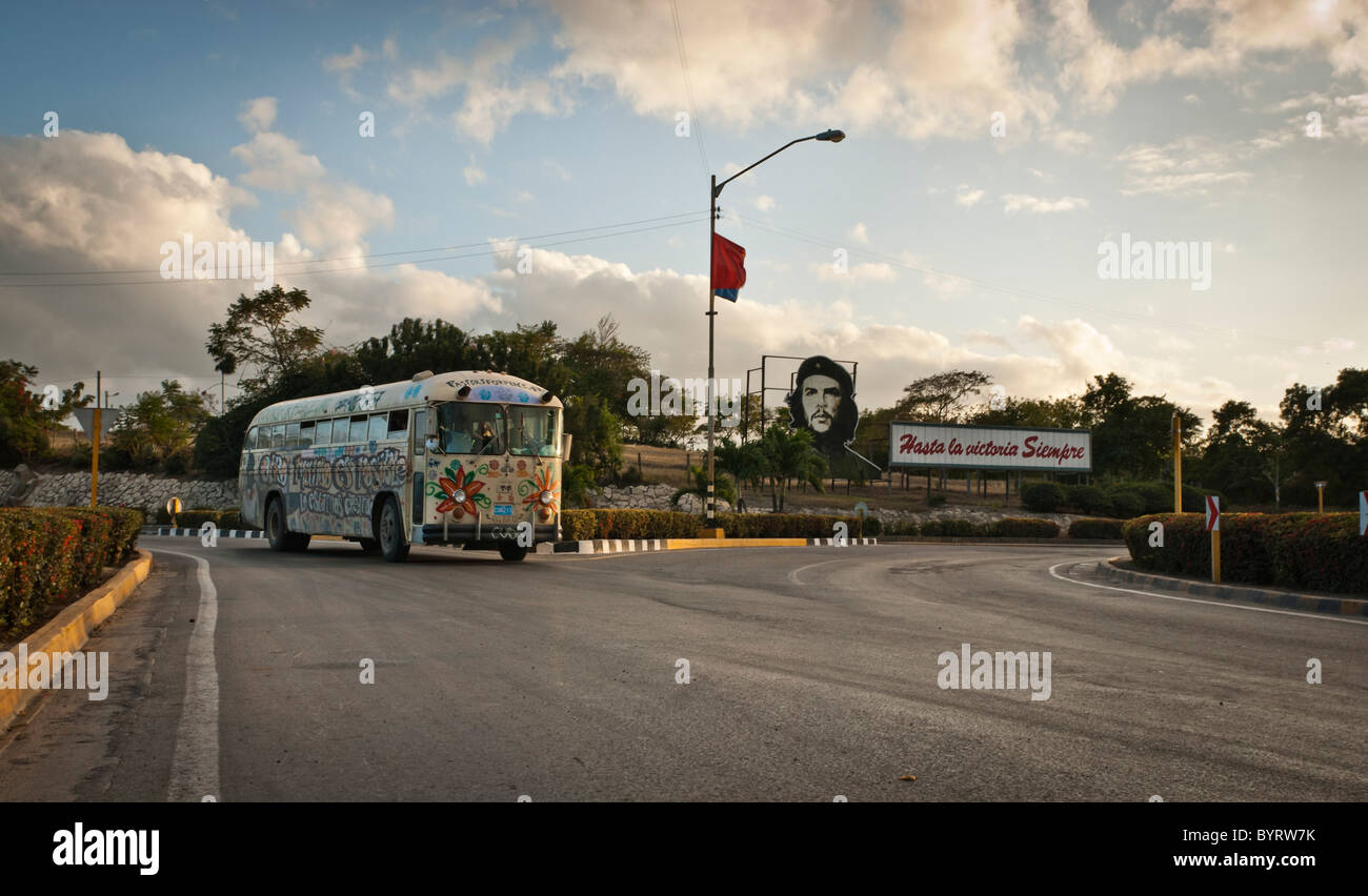 Painted bus driving on a road near Las Tunas near a Che propaganda bill. Las tunas, Cuba, Caribbean. - Stock Image