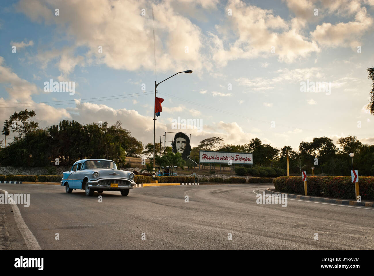 Vintage car driving on a road near Las Tunas near a Che propaganda bill. Las Tunas, Cuba, Caribbean. - Stock Image