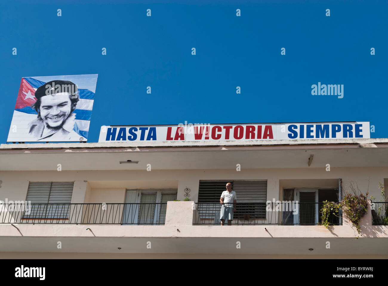 Man on a balcony and a Cuban propaganda sign with the picture of Che an Cuban flag. Camaguey, Cuba, Caribbean. - Stock Image