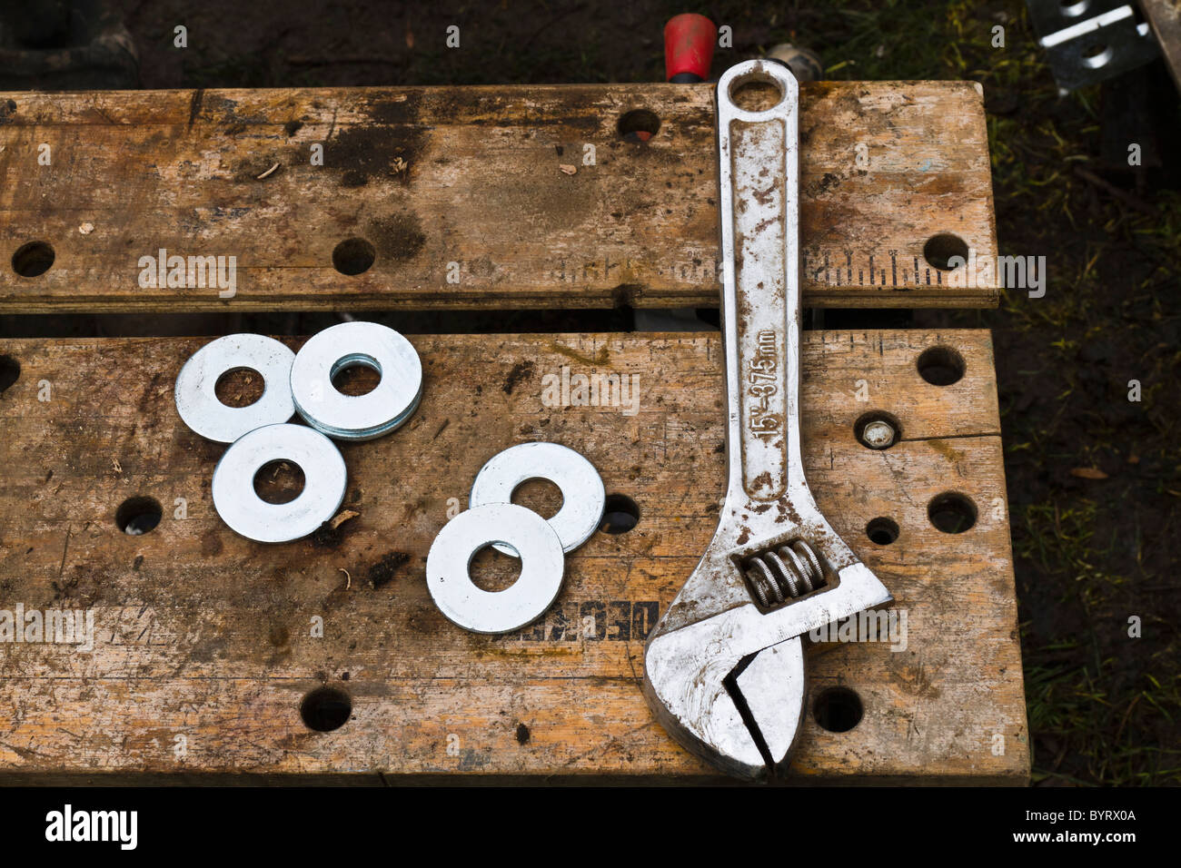 Adjustable spanner and washers on a work bench - Stock Image