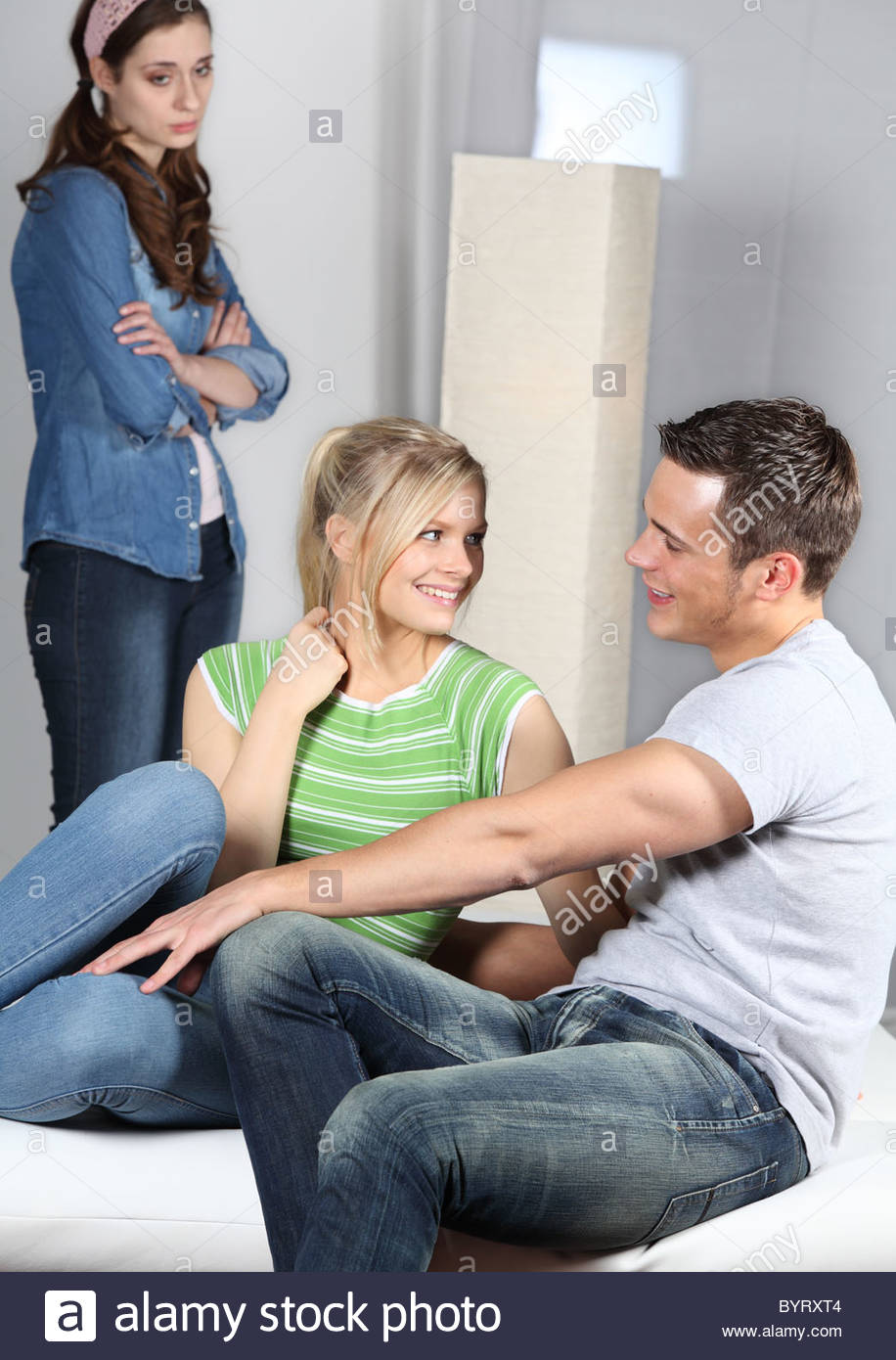 jealous woman looking at a couple - Stock Image