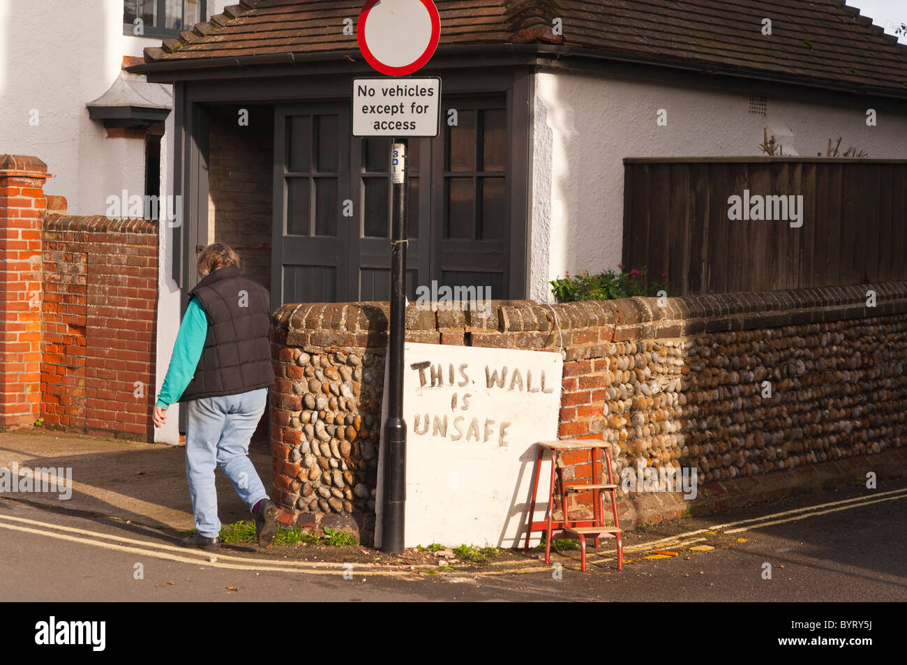 A woman walks past a sign reading unsafe wall in the Uk - Stock Image