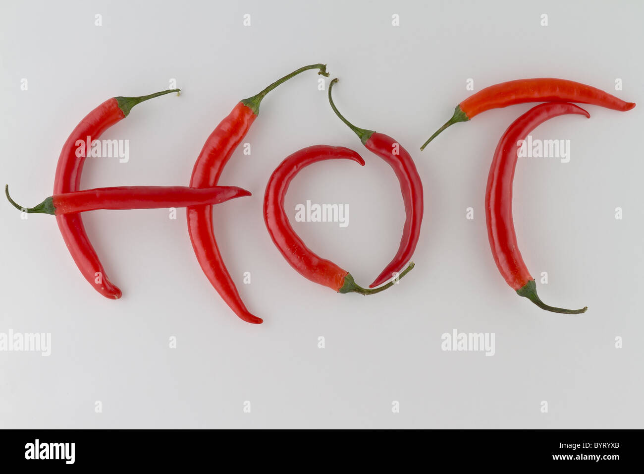 Red hot chili peppers arranged as the word HOT on white background - Stock Image