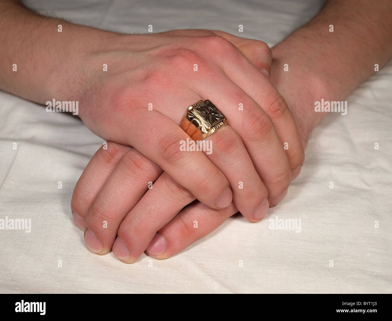 Man\'s hand with a gold ring on his finger against a white tablecloth ...