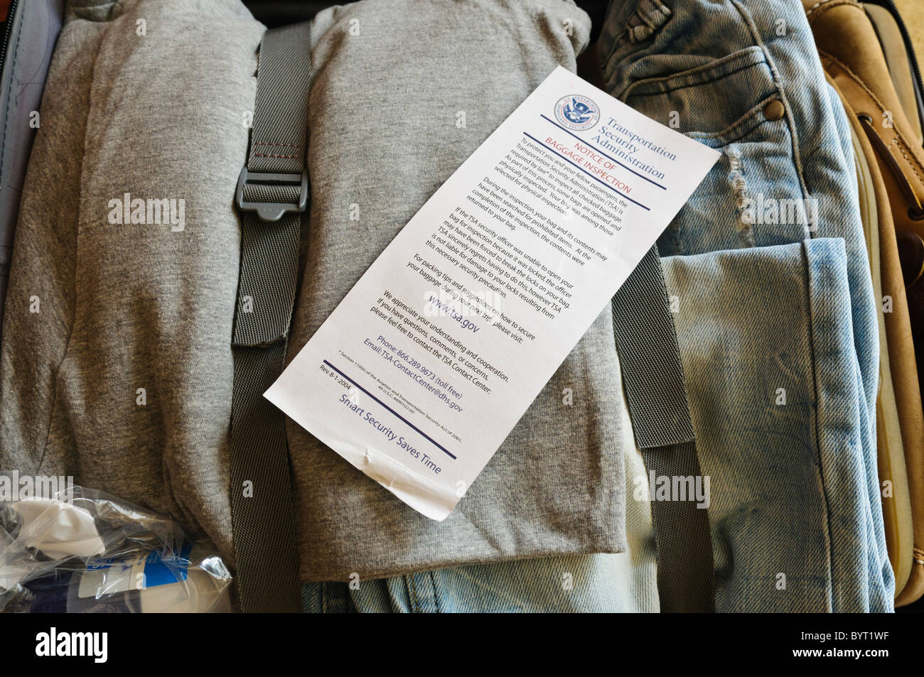 TSA Notice of Baggage Inspection inside a suitcase with clothes - Stock Image