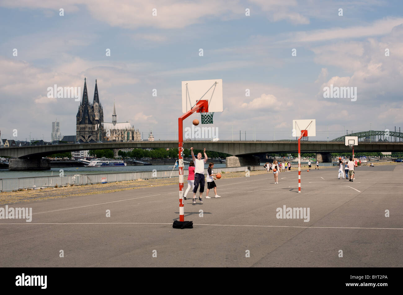 Schoolchildren playing basketball beside the river Rhine, Cologne, Germany. - Stock Image
