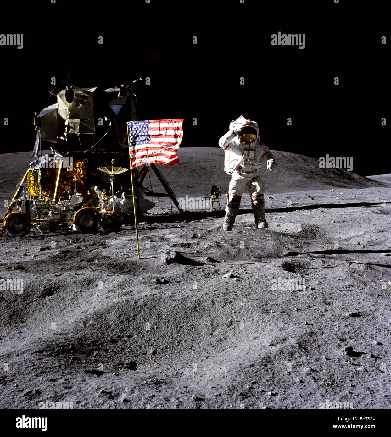Astronaut John W. Young jumps and salutes the U.S. flag during the Apollo 16 lunar landing mission. - Stock Image