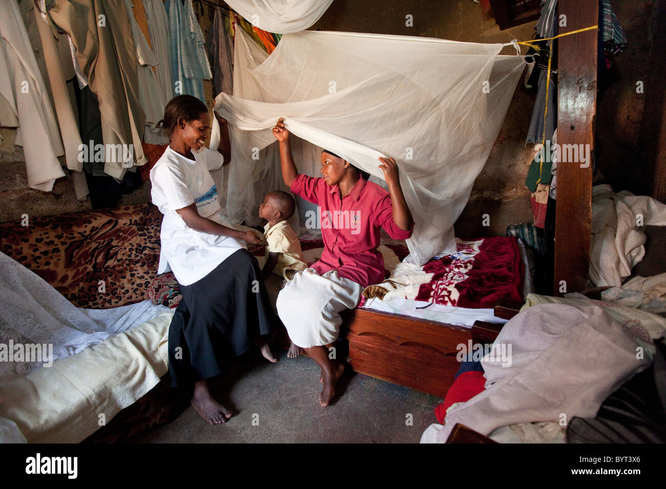 A home health care worker installs a mosquito net in the home of a family in Kampala, Uganda, East Africa. - Stock Image