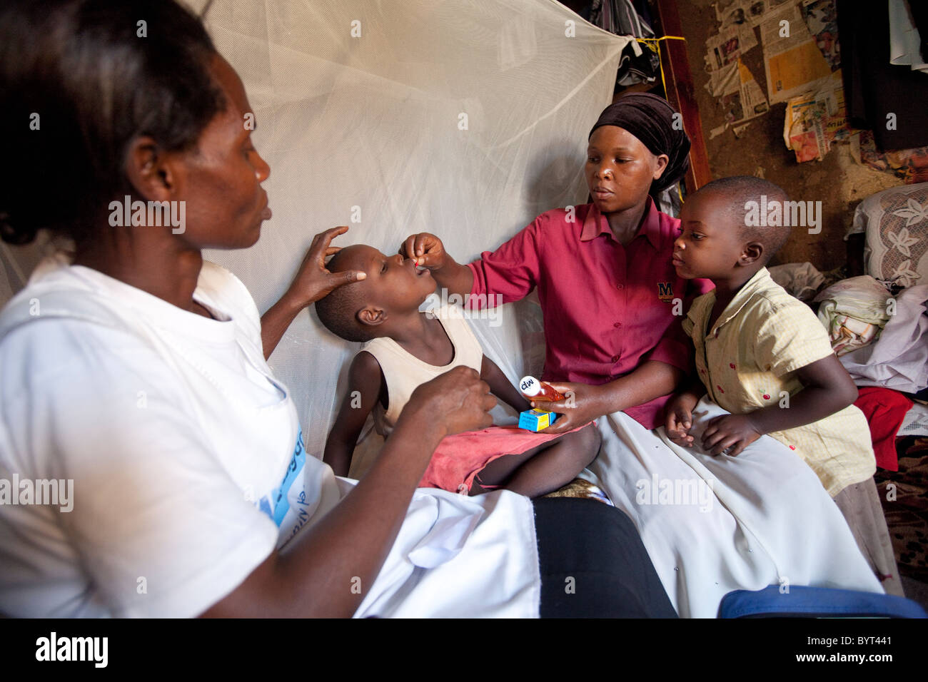 A community health care outreach worker visits an HIV positive family in a slum in Kampala, Uganda, East Africa. - Stock Image