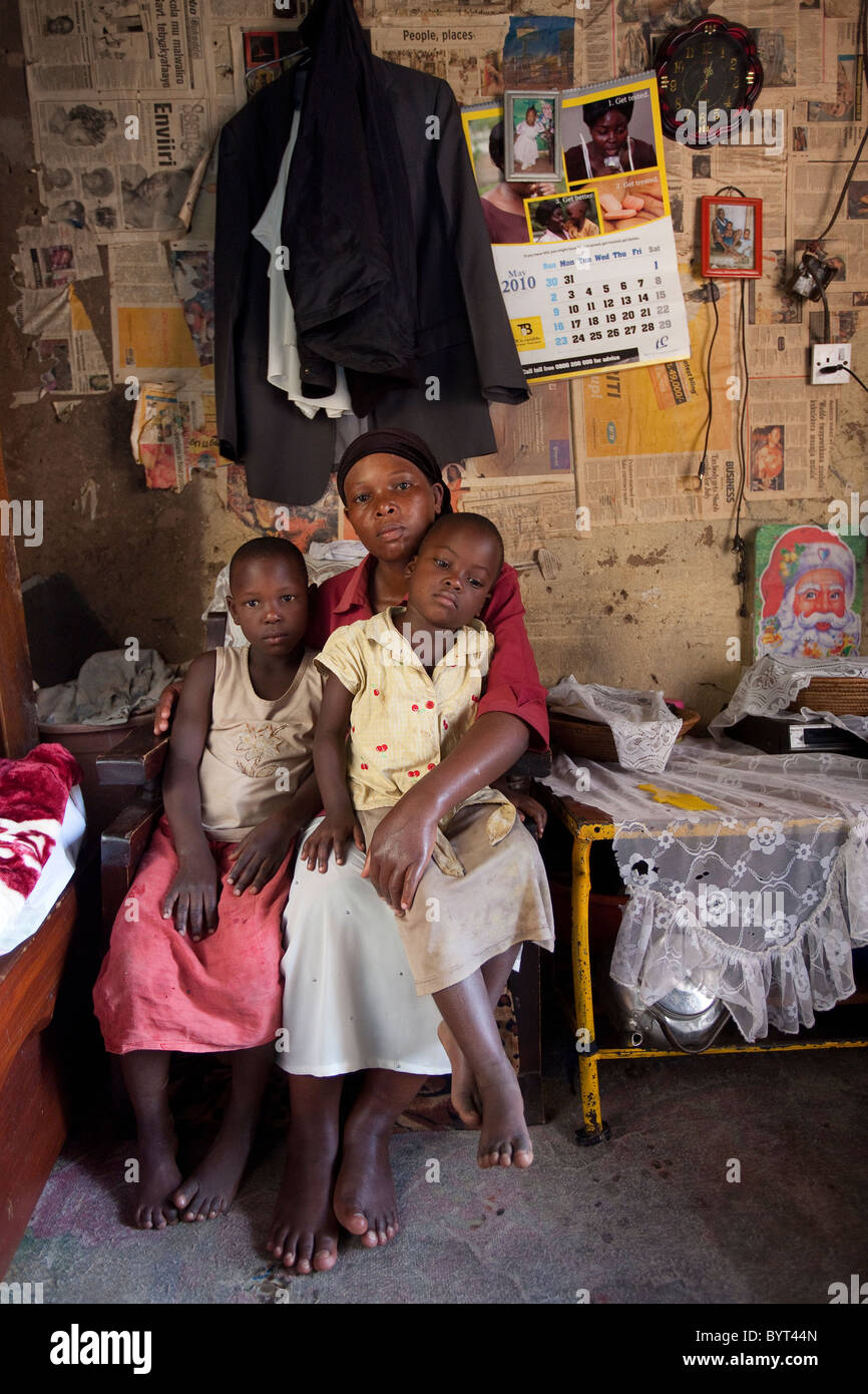 An HIV positive single mother sits in her living room with her two daughters in Kampala, Uganda, East Africa. - Stock Image