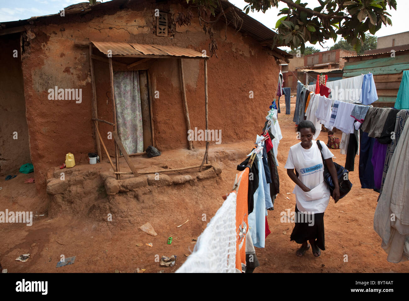 A community health care worker with the NGO Living Goods walks through a slum in Kampala, Uganda, East Africa. - Stock Image