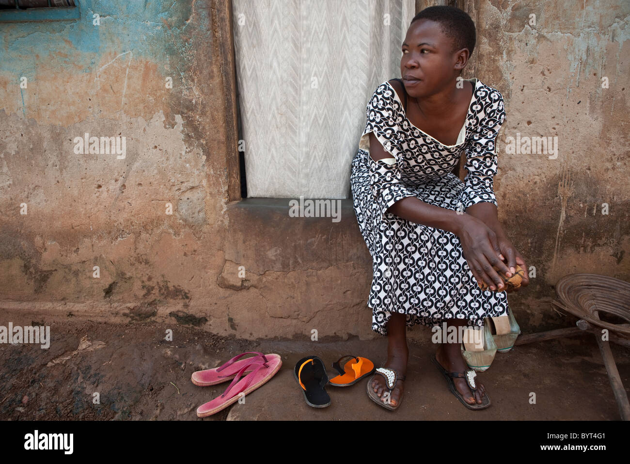 A young urban woman sits outside on her doorstep in Kampala, Uganda, East Africa. Stock Photo