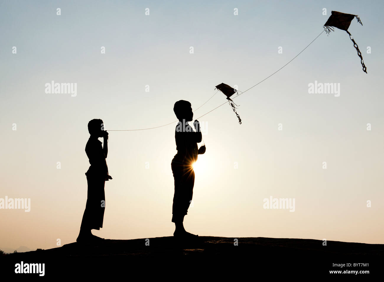 Young indian boys having fun flying handmade paper kites in the indian countryside. Silhouette - Stock Image