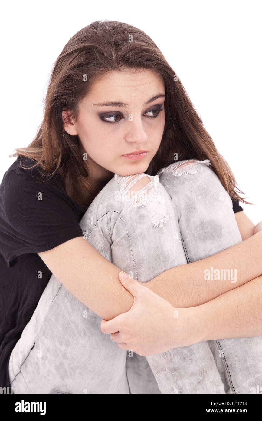 Sad girl teenager sits twining arms about legs - Stock Image