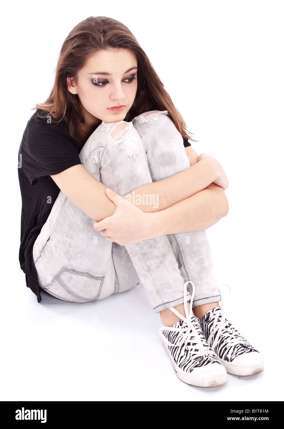 Sad girl teenager sits twining arms about legs. Isolated on a white background. - Stock Image