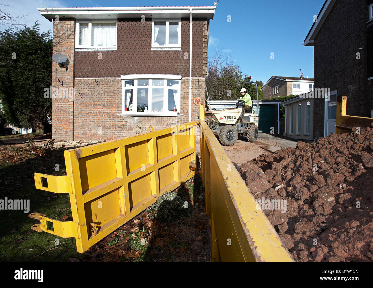 A skip being filled by a dump truck with earth outside a house. - Stock Image