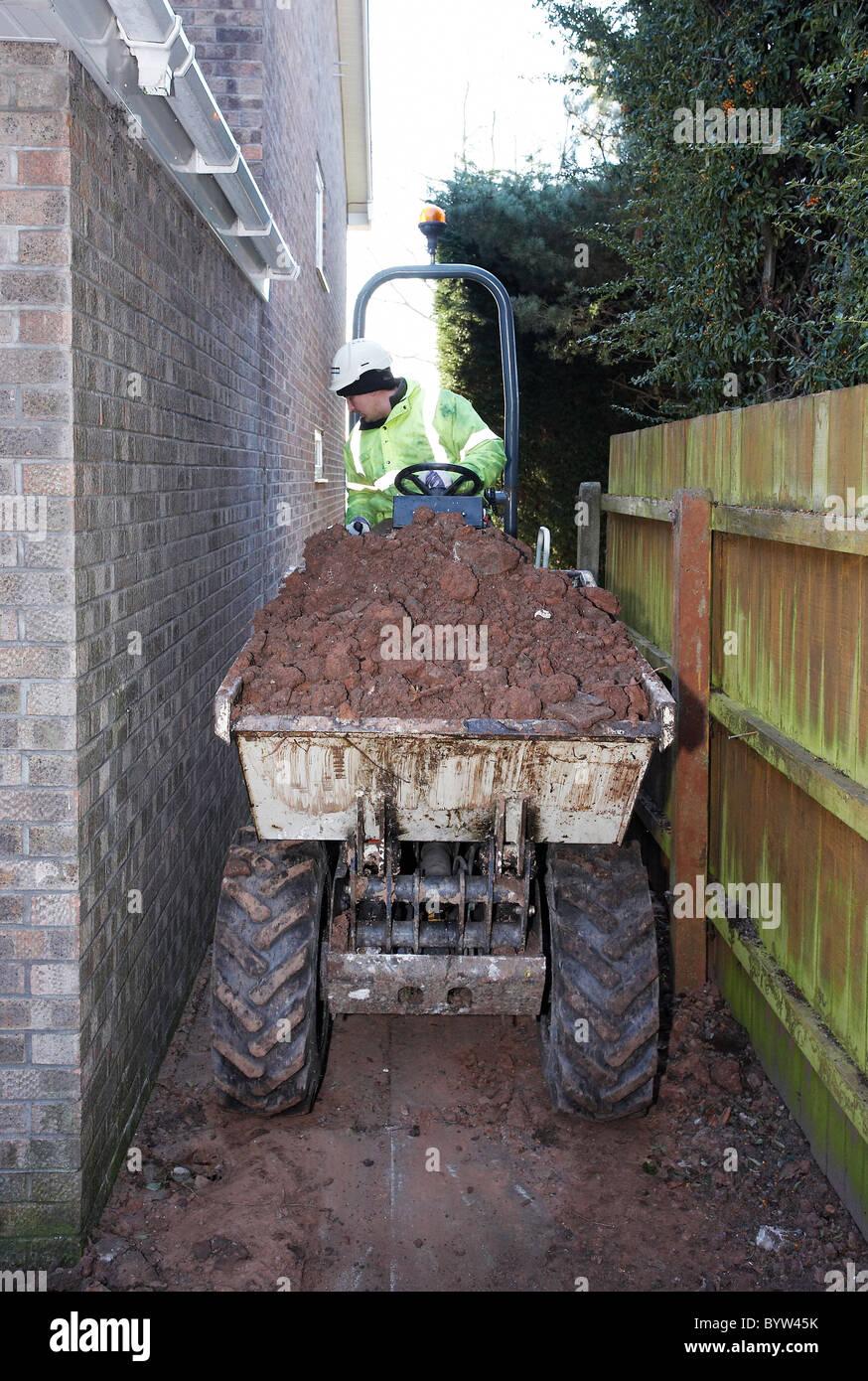 Man reversing a dump truck along side of house. - Stock Image