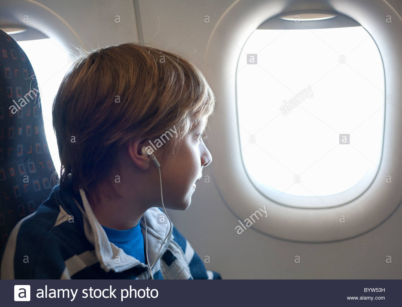 Boy on airplane looking out of window - Stock Image