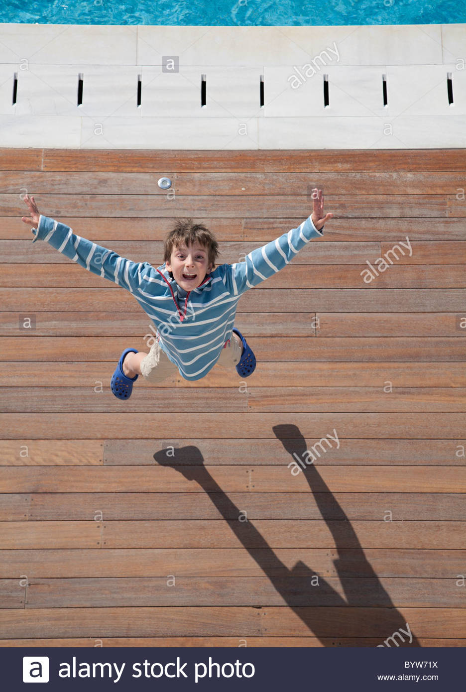 Boy (8-10) leaping into air, aerial view - Stock Image