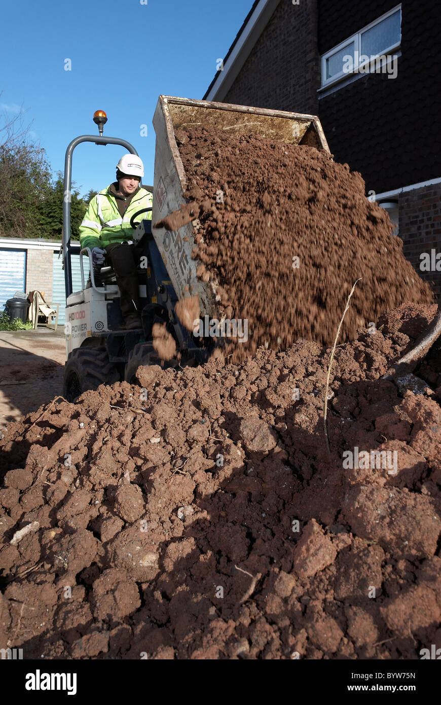 Dump truck emptying its bucket full of earth into a skip - Stock Image